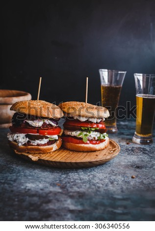 Fresh homemade two veggies burger served on round rustic cutting board over on blue rustic table with two glasses of beer. Rustic dark styling. - stock photo