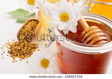fresh honey in glass jars with flowers and pollen on white background - stock photo