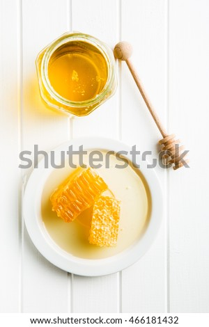 Fresh honey with honeycomb on kitchen table.