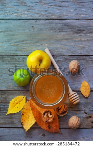 Fresh honey with pollen on an old wooden table. Autumn background with apples, walnuts and honey. Rural motive with food and fallen leaves. - stock photo
