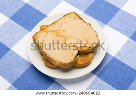 Fresh, hot breakfast toast spread with peanut butter to be consumed during mealtime.  - stock photo