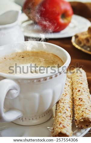fresh hot cup of morning coffee and cookies on a table close-up. selective focus - stock photo