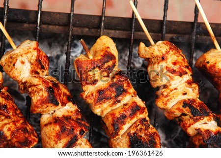 fresh hot grilled chicken shish kebab barbecue on grid over charcoal - stock photo