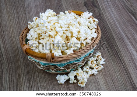 Fresh hot Popcorn in the basket on wood background - stock photo