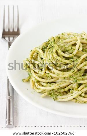 Fresh hot spaghetti with pesto on a plate. - stock photo