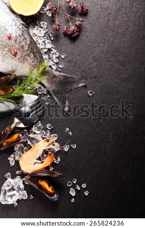 Fresh ingredients for a seafood meal with pink prawns, and the tail of a whole fish with fresh herbs and spices on crushed ice on a slate counter with copyspace - stock photo