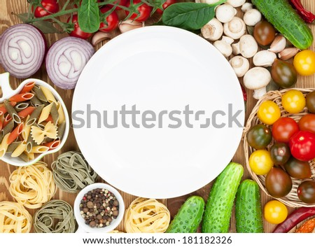 Fresh ingredients for cooking: pasta, tomato, cucumber, mushroom and spices over wooden table background and plate with copy space - stock photo