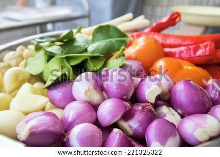 Fresh Ingredients for Cooking Southeast Asian Curry Dish Sauce with Shallots Chili Peppers Ginger Lemon Grass Onions Lime Leaves Garlic Candle Nut Tomato Closeup Macro - stock photo
