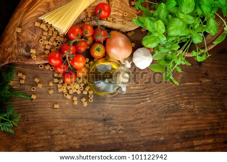 Fresh ingredients for italian cuisine: pasta, tomatoes, basil, olive oil, garlic and onion - stock photo