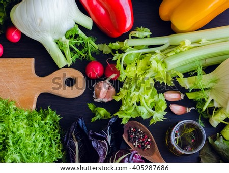 Fresh ingredients for salad: vegetables, olive oil and spices over wooden table background with cutting board. Healthy eating. Vegetables background. Healthy food. Food flat lay. Top view.  - stock photo
