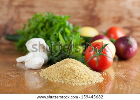 Fresh ingredients for tabbouleh on a wooden table - stock photo