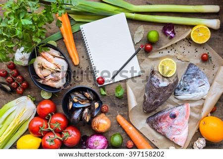 Fresh ingredients to cook fish soup, bouillabaisse: fish heads, onion, lime, lemon, leak, parsley, tomatos, carrot, celery, mussels, shrimps. Top view, horizontal composition - stock photo