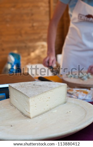 Fresh Italian cheese on wooden dish at local market. Copy space. - stock photo