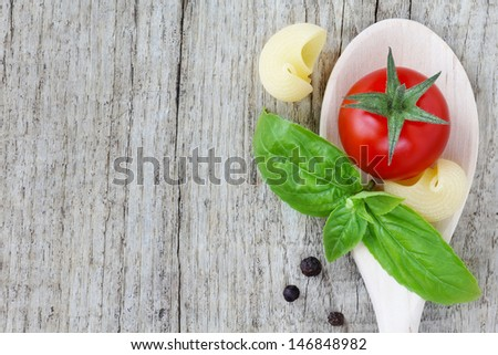 Fresh Italian cuisine ingredients - cherry tomato, green basil sprig, black pepper and pasta - in a wooden spoon over rustic wooden background. With copy space - stock photo