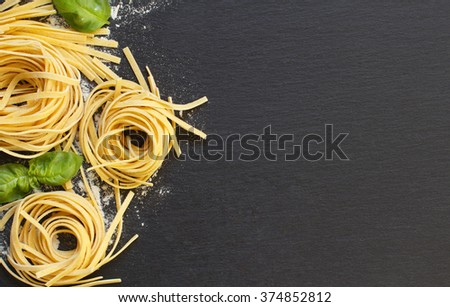 Fresh italian pasta and basil on a dark background - stock photo