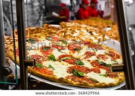 Fresh Italian pizza in New York City pizzeria window - stock photo