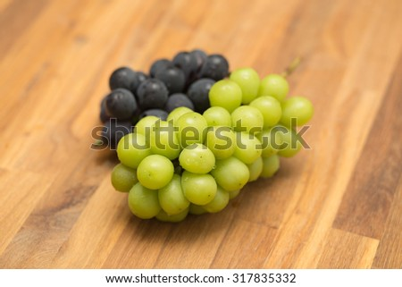 Fresh Japanese muscat and Kyoho grapes on wooden table - stock photo