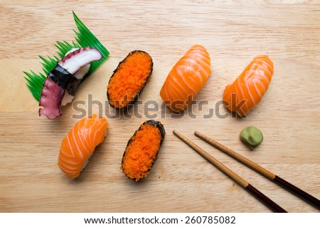 Fresh japanese sushi with wasabi and chopsticks on wood background - stock photo