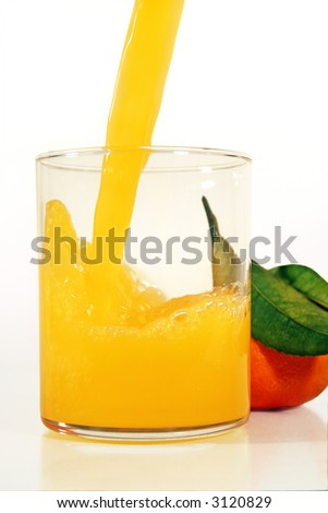 fresh juice being poured into a glass with a whole orange behind - stock photo