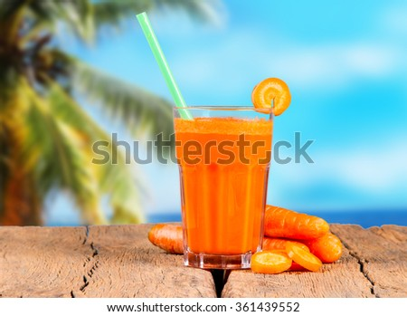 Fresh juice,carrot on wooden table with tropical beach background - stock photo