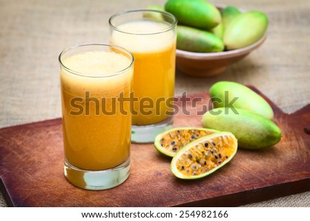 Fresh juice made of the Latin American fruit called banana passionfruit (lat. Passiflora tripartita) (in Spanish mostly tumbo, curuba, taxo) (Selective Focus, Focus on the front of the first glass) - stock photo