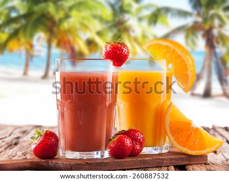 Fresh juice, mix fruits, strawberry and orange drinks on wood plants with tropical beach background - stock photo