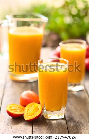 Fresh juice out of tamarillo fruits (lat. Solanum betaceum) on a table outdoors (Selective Focus, Focus on the front rim of the glass) - stock photo