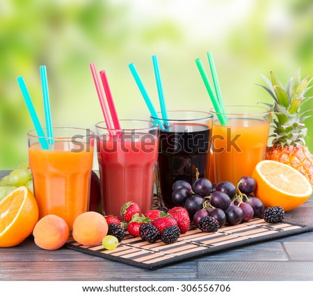Fresh juice with fruits on wooden table with nature green background - stock photo