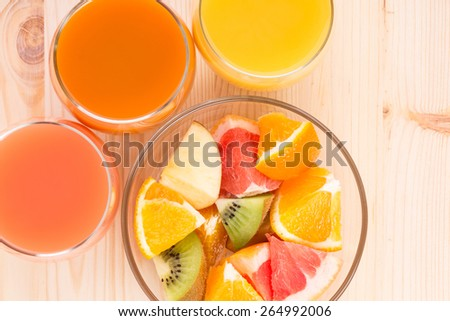 Fresh juices in three glasses with fruit salad. Vitamins background top view image - stock photo