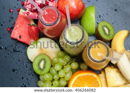 Fresh Juices Smoothie Red Green Yellow Tropical Fruits Water Melon Strawberry Apple Kiwi Orange Mango Banana Pine Apple Pomegranate Grape Selective focus Bottles Top View - stock photo