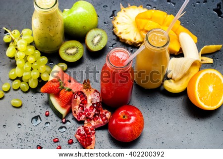 Fresh Juices Smoothie Three Bottles made Red Green Orange Fruits Water Melon Strawberry Apple Kiwi Grapes Orange Mango Pomegranate Tropical Selective focus Black Background - stock photo