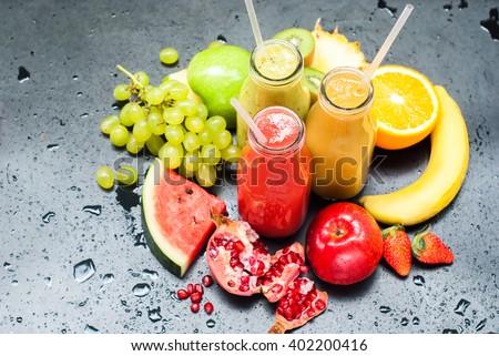 Fresh Juices Smoothie Three Bottles made Red Green Orange Fruits Water Melon Strawberry Apple Kiwi Grapes Orange Mango Pomegranate Tropical Selective focus - stock photo