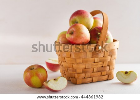 Fresh juicy apples in basket on wooden background, selective focus - stock photo