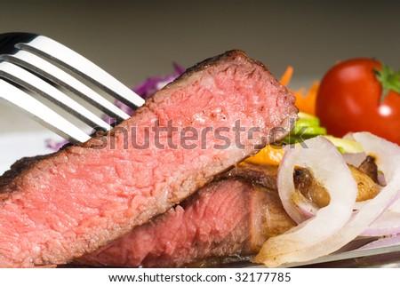 fresh juicy beef ribeye steak sliced ,with lemon and orange peel on top  and vegetable beside - stock photo