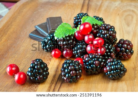 Fresh juicy blackberries and cranberries with chocolate and mint on wooden dish. Closeup. - stock photo