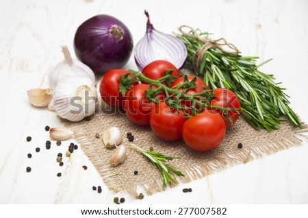 Fresh juicy cherry tomatoes with spices on white wooden background - stock photo