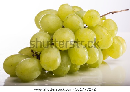 Fresh juicy grapes on a white table against a white background - Grapes white - Dripping water on table - A bunch of grapes - Juicy fresh grapes - macro photography - stock photo