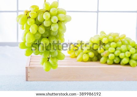 Fresh juicy grapes on a wood table against a white window background - Grapes white - Dripping water on table - A bunch of grapes - Juicy fresh grapes - macro photography - stock photo