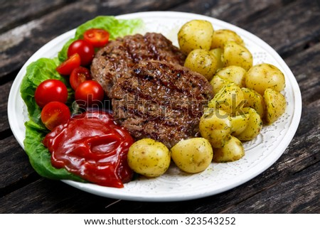 Fresh juicy grill burgers, served with ketchup, young potatoes, tomatoes and vegetables. On wooden table. - stock photo