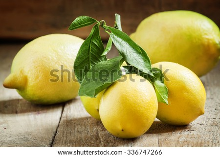 Fresh juicy lemons with leaves on the old wooden table, selective focus - stock photo