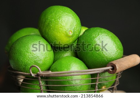 Fresh juicy limes in basket on wooden table, on dark background - stock photo