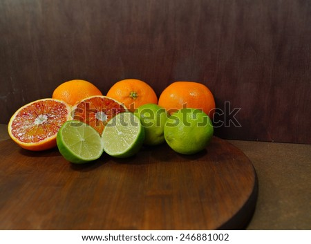 Fresh juicy limes on old wooden table and red oranges - stock photo