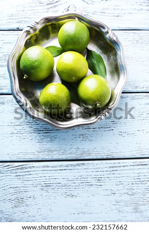 Fresh juicy limes on plate on wooden background - stock photo