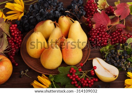 Fresh juicy pear; Pears on clay plate; autumn still life; Autumn background; Cover for the fall menu; grapes; heather; autumn grass and fruit on wooden background;  substrate for the menu; cookbook;   - stock photo