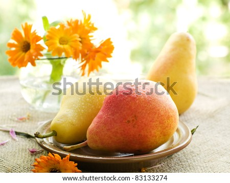 Fresh juicy pears on plate with flower on background. Selective focus - stock photo