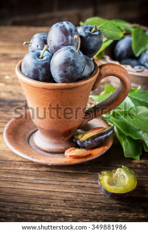 Fresh juicy plums with leaves in a ceramic pot on a simple handmade wooden background. Concept of healthy food with seasonal ingredients. selective Focus - stock photo