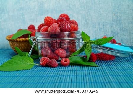 Fresh juicy raspberries in glass dish . Selective focus - stock photo