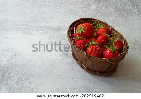 Fresh juicy strawberries in an old wicker basket - stock photo