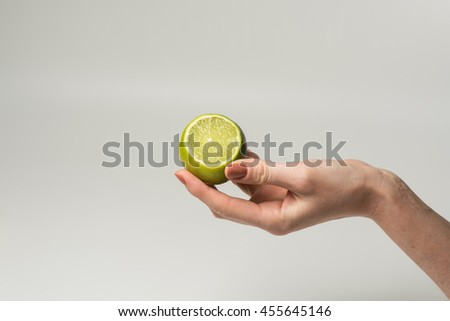 Fresh juicy tasty green lime in a Female hand on white background. - stock photo