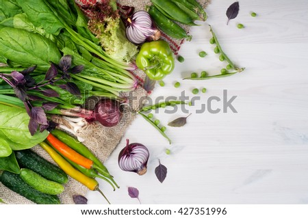Fresh juicy vegetables such as hot pepper, purple onion, young peas, peppers and spinach on a white wooden background. Place for writing text. Vegan concept. Fresh farm products - stock photo